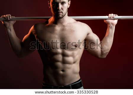 One sexual strong young man with muscular body in jeans holding iron crossbar standing posing in studio on red background, horizontal picture - stock photo