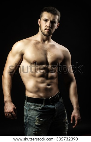 One sexual strong young man with muscular body in jeans looking forward standing posing in studio on black background, vertical picture - stock photo