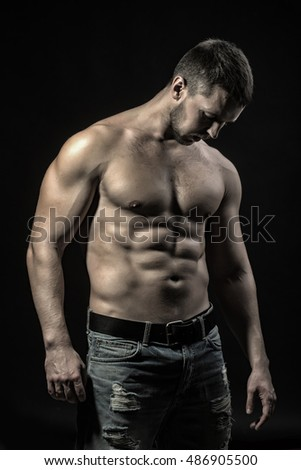 One sexual strong young man with muscular body in jeans looking forward standing posing in studio on black background, vertical picture