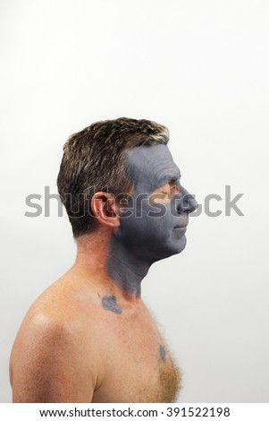 One shirtless caucasian man right side view wearing a drying dark gray charcoal tea tree oil face mask as a treatment for his facial skin. A man wearing a clay beauty mask