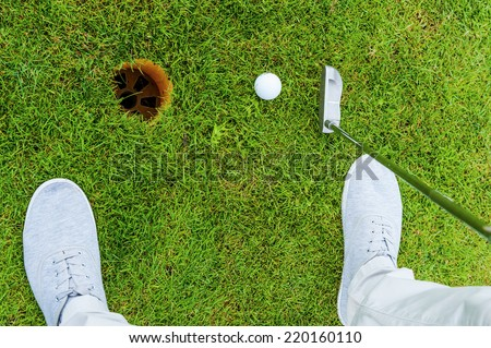 One shot to success. Top view of golfer putting while standing on green and near the hole - stock photo