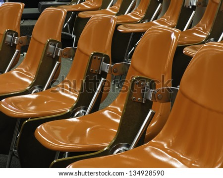 One size fits all: Identical shiny hard orange molded seats in lecture hall - stock photo