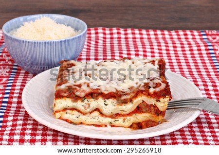 One slice of homemade lasagna with a side bowl of grated parmesan cheese. - stock photo