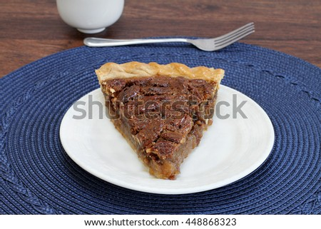 One slice of pecan pie, point forward on a white plate.  Close up, copy space.