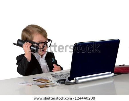 One small little girl (boy) calling phone, wearing black suit and glasses. Computer, credit cards are on table. Business concept. Isolated object. - stock photo