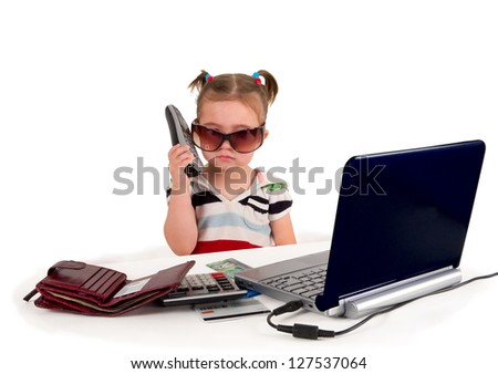 One small little girl wearing t-shirt. Phone, credit cards, gift cards, calculator, notebook on the table. Canadian $20 bank notes examination card on the table. Business concept. Isolated object.