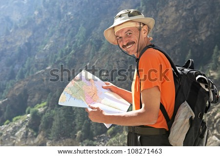 One smiling happy tourist traveller hiker with route map in Himalayas mountains