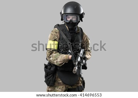 One soldier holding assault rifle ak-74. Uniform conforms to special services FSB of the Russian Federation. Shot in studio. Isolated with clipping path on grey background