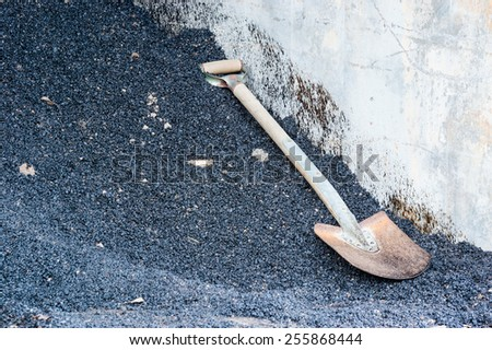 One spade on pile of tarmac or oil gravel. Concrete wall beside spade with oil stain on.