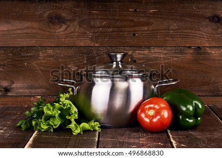 One stainless steel pot with glass cap standing on old grunge wooden table. Fresh vegetables. Tomato, parsley, salad and green sweet pepper