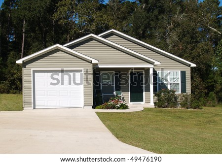One story residential low income home with gray vinyl siding and front entry garage. - stock photo