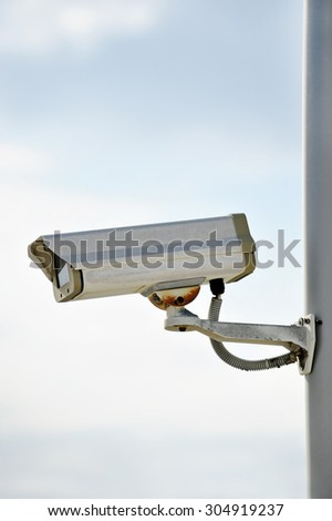 One surveillance camera on a pole with blue sky on background