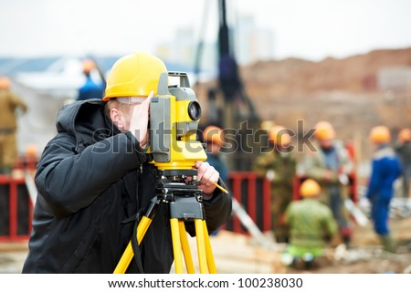 One surveyor worker working with theodolite transit equipment at construction site outdoors - stock photo