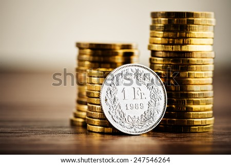 one swiss frank coin and gold money on the desk