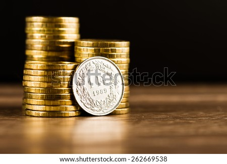 one swiss frank coin and gold money on the desk - stock photo