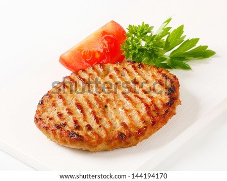 one thin grilled burger with tomato and herbs - stock photo