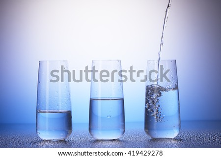 One-third full, half-filled and two-thirds full drinking glasses with reflection in drops of water on white and blue background. Water pouring into last one. - stock photo