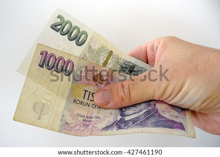One thousand and two thousand czech crown bank-notes in white man hand. Pay bills with money. Currency concept - stock photo