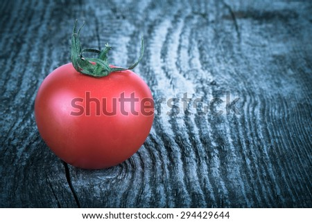 One tomato with dew on its side on an old gray cracked wooden table. Background. Tinted. - stock photo