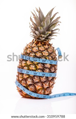 One tropical fresh big fruit of pineapple with blue measuring tape as diet symbol standing on white studio background closeup, vertical picture - stock photo