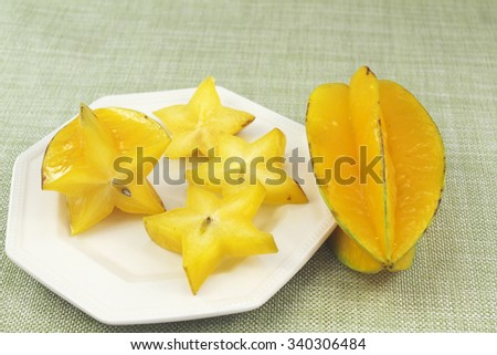 One tropical yellow carambola star fruit with three star shaped pieces cut from it on a small white plate next to a whole raw starfruit on a green cloth place mat closeup.