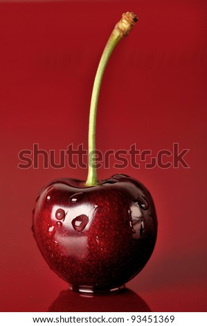 One vertical cherry on the red background - stock photo