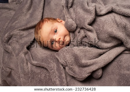 One very cute three-month old baby in a grey blanket. - stock photo
