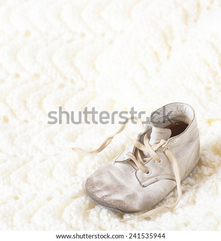 One Vintage Leather Infant's Shoe on a Hand Knitted  Cream Afghan Background with room or space for copy, text, your words.  Square crop, high key with white warm tones - stock photo