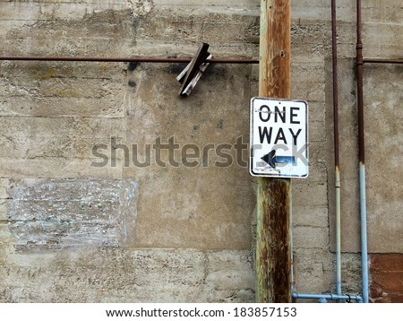 One way sign in an urban alley along an old building wall.