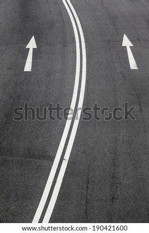One-way signs and double middle lines on a road/One Way Road - stock photo