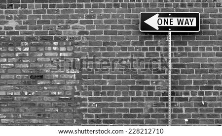 one way street sign in front of brick wall - stock photo
