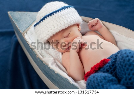 One week old newborn baby boy wearing a white and blue sailor hat. He is sleeping on his back in a tiny boat. - stock photo