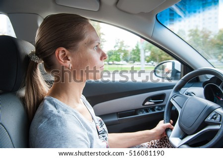 one white blond attractive young woman drives a car
