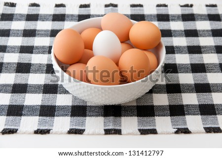 One white egg between brown eggs. selective focus