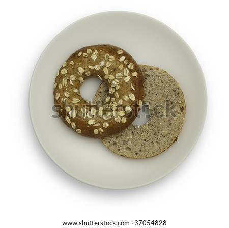 One Whole Grain Bagel on a White plate, isolated on white background. The Bagel is cut in half and is arranged so the inside of one half is visible. Saved with clipping path.