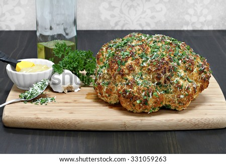 One whole head of roasted cauliflower on cutting board with roasting ingredients.