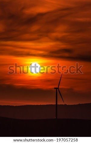 One wind turbine standing on the hill against a dramatic sunset lighted sky in the background - stock photo