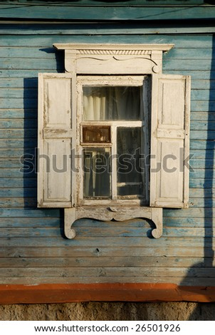 One window with open white wooden shutters and carved decorations