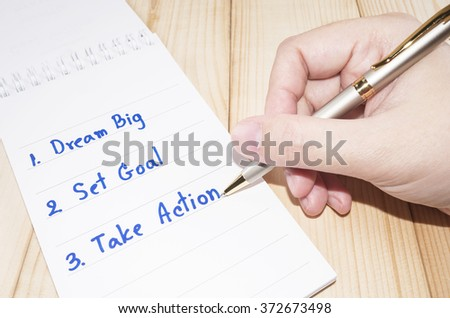 "One woman hand is writing ""Dream Big, Set Goal, Take Action"" on notebook with wooden background (Business concept)"