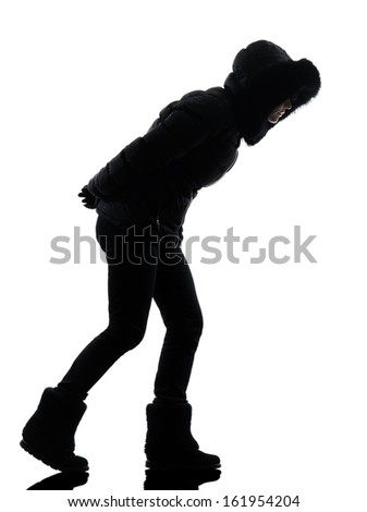 one  woman in winter coat walking windy silhouette on white background