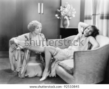 One woman massaging a friends leg - stock photo