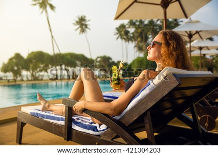 One woman near the swimming pool in hotel with cocktail