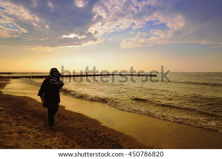 One woman on the beach on sunset. - stock photo