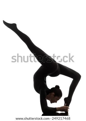 one  woman practicing gymnastic yoga Eka Pada Viparita Dandasana in silhouette on white background - stock photo