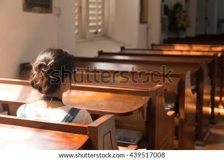 One woman sitting in church. The sun shines through the window to the left of the church. - stock photo