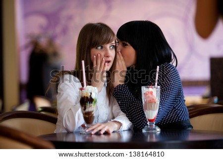one woman whispering something to friend - stock photo
