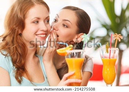 one woman whispering something to friend. two girls sitting in cafe and drinking juice - stock photo