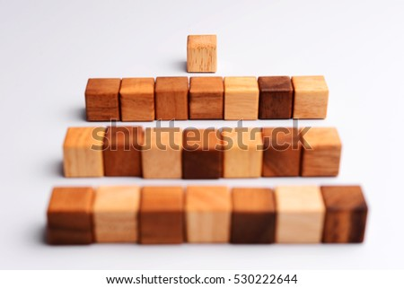 One wood block standing in front of group of cube wood block which standing in line or row, metaphor to leader stand in front of many follower. Leadership concept. Selective focus, gray background.