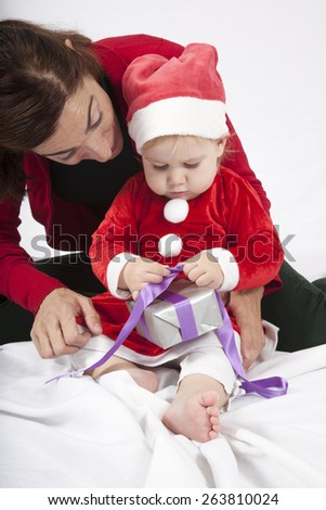 one year age caucasian blonde baby Santa Claus disguise with brunette woman mother red cardigan green trousers opening silver wrapped paper box gift Christmas on white background - stock photo