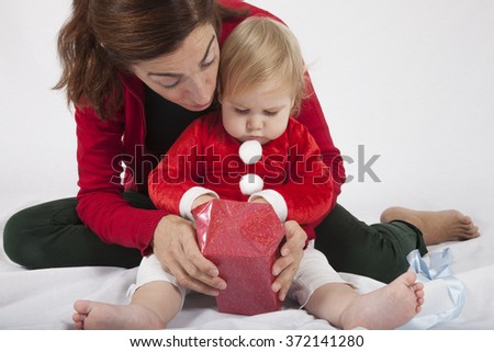 one year age caucasian blonde baby Santa Claus disguise with brunette woman mother red cardigan green trousers opening Christmas box gift on white background - stock photo